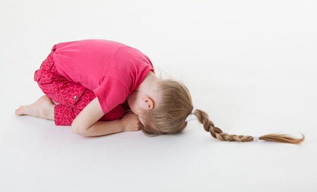 disinclination: Little girl bending and closing her eyes in the squatting position, white background