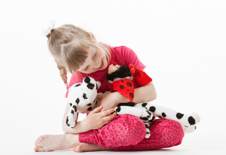 upgrowth: Pretty little girl playing with plush toys, white background