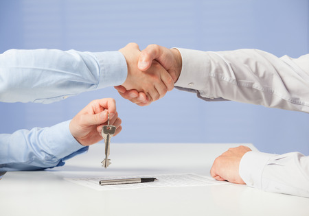real estate agent: Businessman passing keys to his partner and shaking his hand, blue background Stock Photo