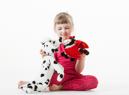 plush toys: Pretty little girl playing with plush toys, white background