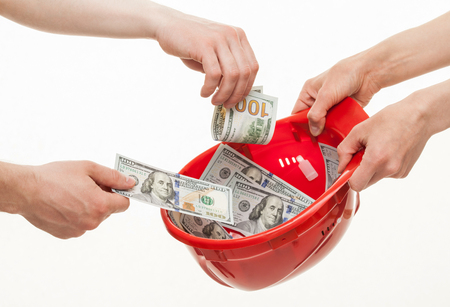 instance: Human hands putting dollars in a red hard hat , white background