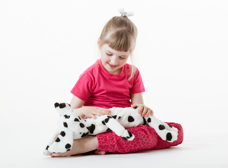 plush toy: Pretty little girl playing with plush toy, white background