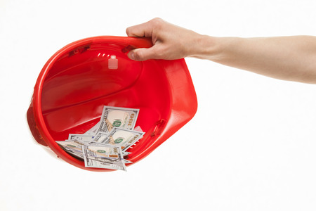 Human hand holding a red hard hat with money, white background Stock Photo