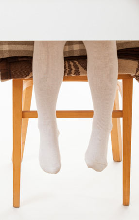 panty hose: Little child sitting on the high chair, white background