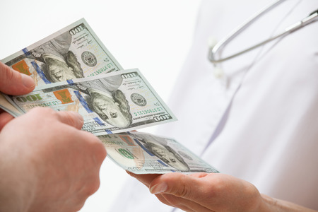 doctor money: Patients hand giving a money to doctor, white background
