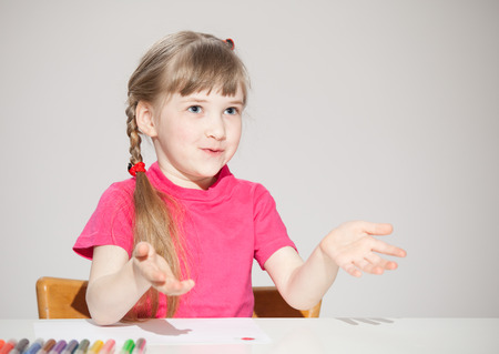 former years: Pretty little girl sitting at the table and showing her empty palms, neutral background Stock Photo