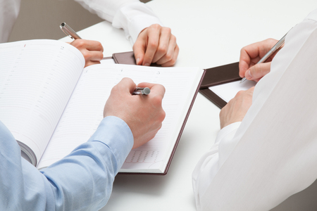 datebook: Businessman making notes in a datebook - closeup shot Stock Photo