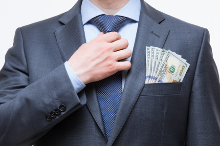 corruptible: Unrecognizable businessman setting  the tie straight with money in the pocket