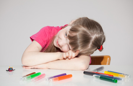 Smiling little girl sitting at the table and dreaming, gray background Stock Photo