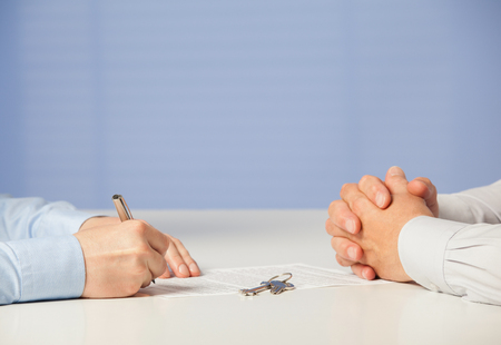 real business: Two businessmen discussing a deal and signing a contract, blue background