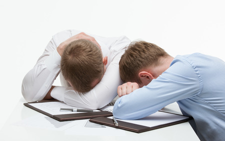 slump: Weary businessmen sitting at the table, white background Stock Photo