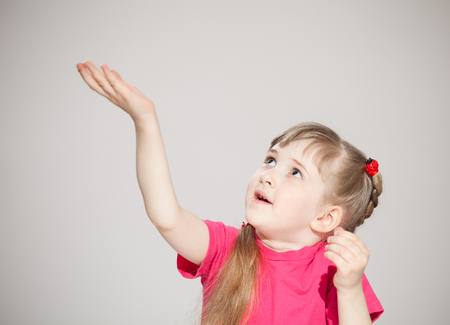 Happy little girl reaching out her palm and catching something, neutral background Reklamní fotografie