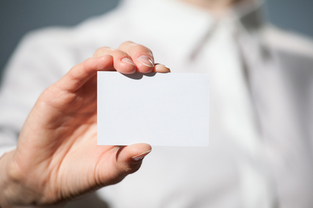 Businesswoman's hand showing business card on dark background