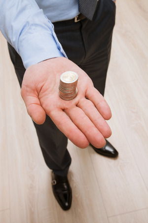 hand up: Businessman holding euro coins - closeup shot