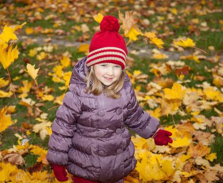 upbringing: Beautiful little girl walking among autumn leaves
