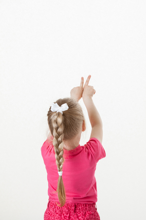 former years: Caucasian little girl turning back and indicating something up, white background Stock Photo