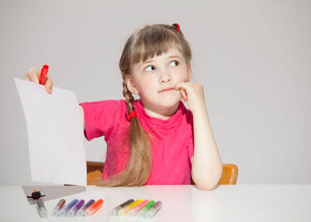 industrious: Pretty little girl sitting at the table and showing empty sheet of a paper, neutral background