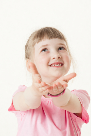 devise: Happy little girl reaching out her palms and catching something, white background Stock Photo