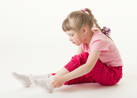 Pretty little girl trying on sock, white background Фото со стока