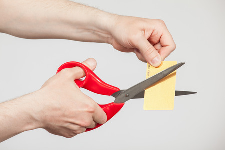 dissect: Male hands holding scissors and cutting a plastic card, neutral background