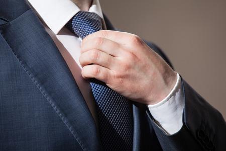 traje formal: El hombre de negocios ajustándose la corbata - disparo de cerca Foto de archivo