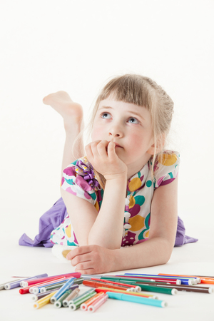 upgrowth: Little girl lying on the floor and thinking, white background