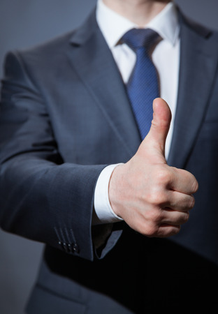 assent: Unrecognizable businessman showing thumb up, dark  background