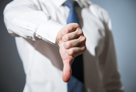 THUMBS DOWN: Unrecognizable businessman showing thumb down, dark background Stock Photo