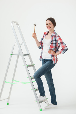 stepladder: Young woman standing near the stepladder and holding a hammer, white background Stock Photo