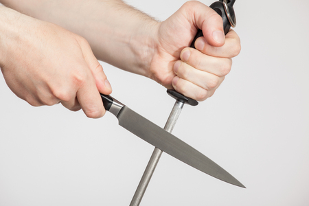 Unrecognizable man sharpening a large knife, neutral background Stock Photo