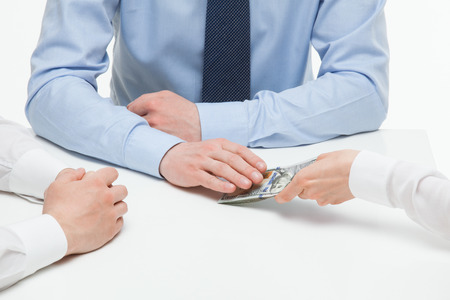 corruptible: Female hand shoving money under business partners hand, white background Stock Photo
