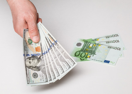 predilection: Businessmans hand holding many dollars, neutral background Stock Photo