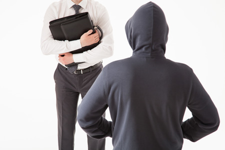 larceny: Businessman trying to hide his briefcase by unknown man, white background