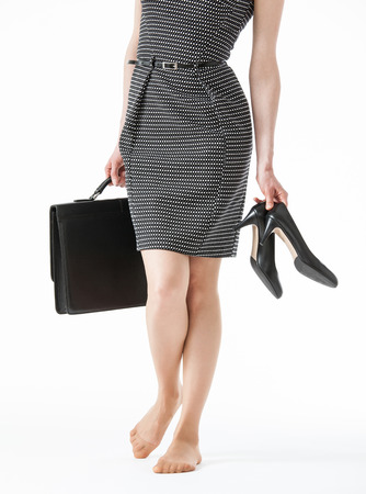 chafe: Young woman holding her black shoes and a briefcase, white background Stock Photo
