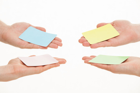 reaching out: Human hands reaching out colorful paper cards on white background Stock Photo