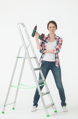 stepladder: Young woman standing near the stepladder and holding a screwdriver, white background Stock Photo