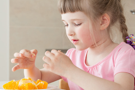 Happy little girl eating a tasty orange at home photo