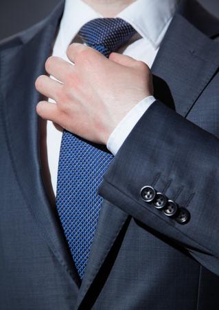 adjusting: Businessman adjusting his tie - closeup shot