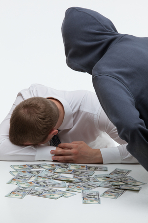 Unrecognizable robber bending over the sad businessman and money , white background
