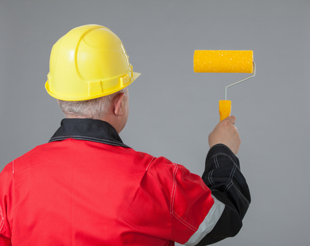 colourer: Painter in an yellow helmet holding a yellow roller, rear view