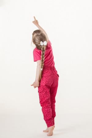 barefooted: Barefooted little girl turning back and indicating something up, white background