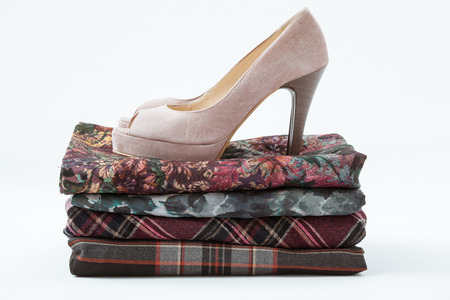 tog: Beige shoe on the pile of clothers, white background Stock Photo