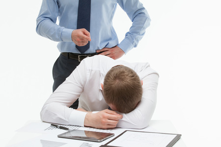 slump: Weary clerck sitting at the table and his dissatisfied boss standing behind , white background