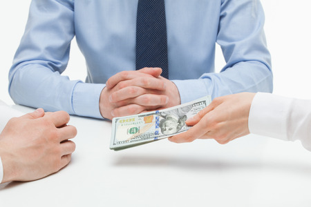 venality: Female hand shoving money under business partners hand, white background Stock Photo