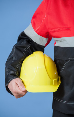 yellow hard hat: Fragment of a builder holding yellow hard hat, grey background