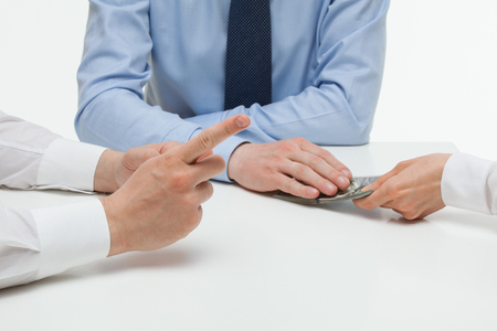 subornation: Female hand shoving money under business partners hand, closeup shot