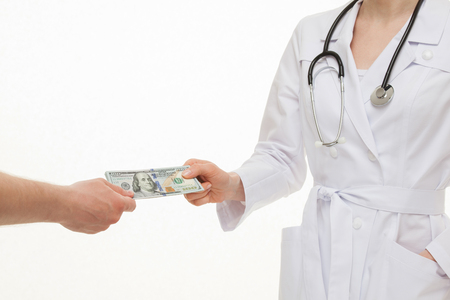 graft: Patients hand giving  money to doctor, white background Stock Photo