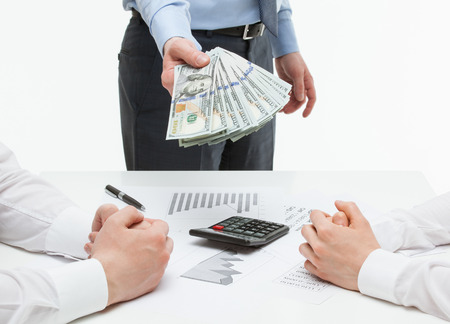 collaborator: Businessman reaching out money for his business partner, white background