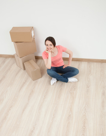 upper floor: Happy young woman sitting on the floor among boxes