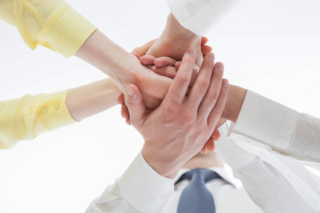 uniting: Business people uniting their hands - gesture of a uniion, view from below